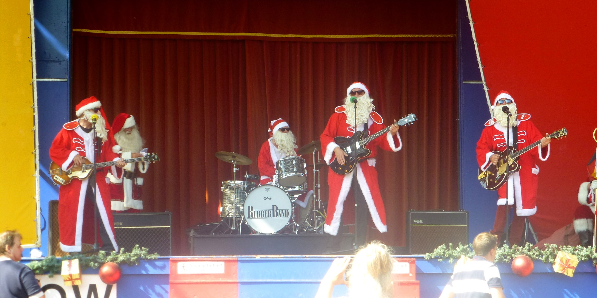 a band of guys all dressed as Santa plays music