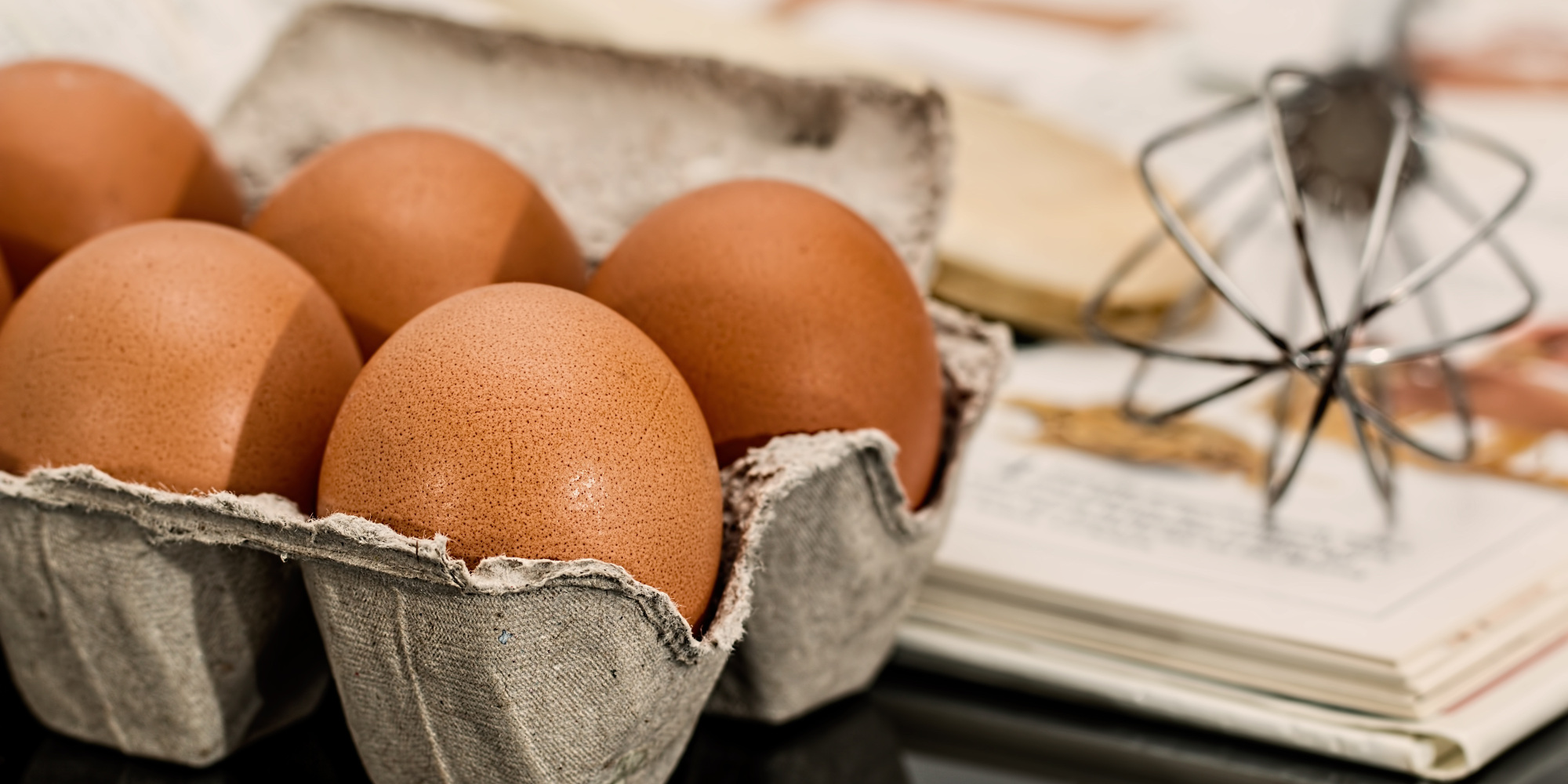 eggs and a whisk are placed near recipes on paper