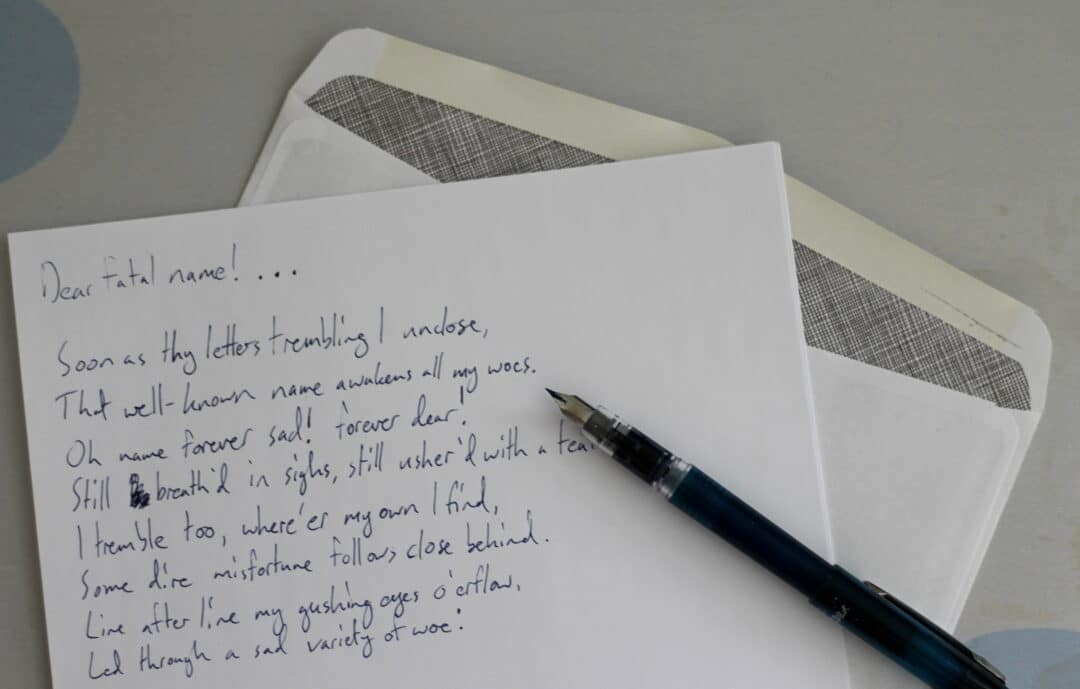 a letter, pen and paper sit on a desk. the letter contains lines from Alexander Pope's poem Eloisa to Abelard