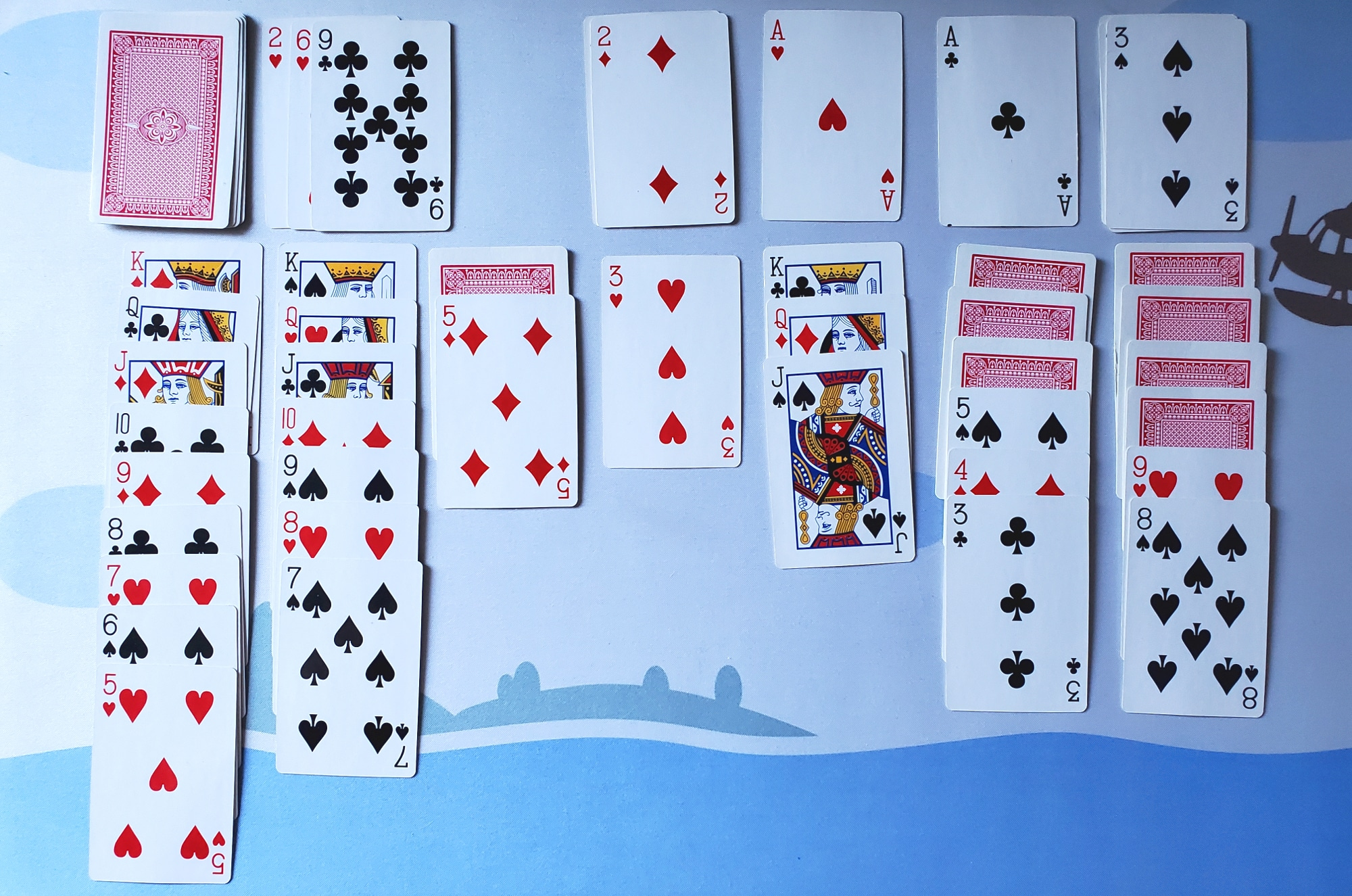 a game of solitaire is played with real cards on a table