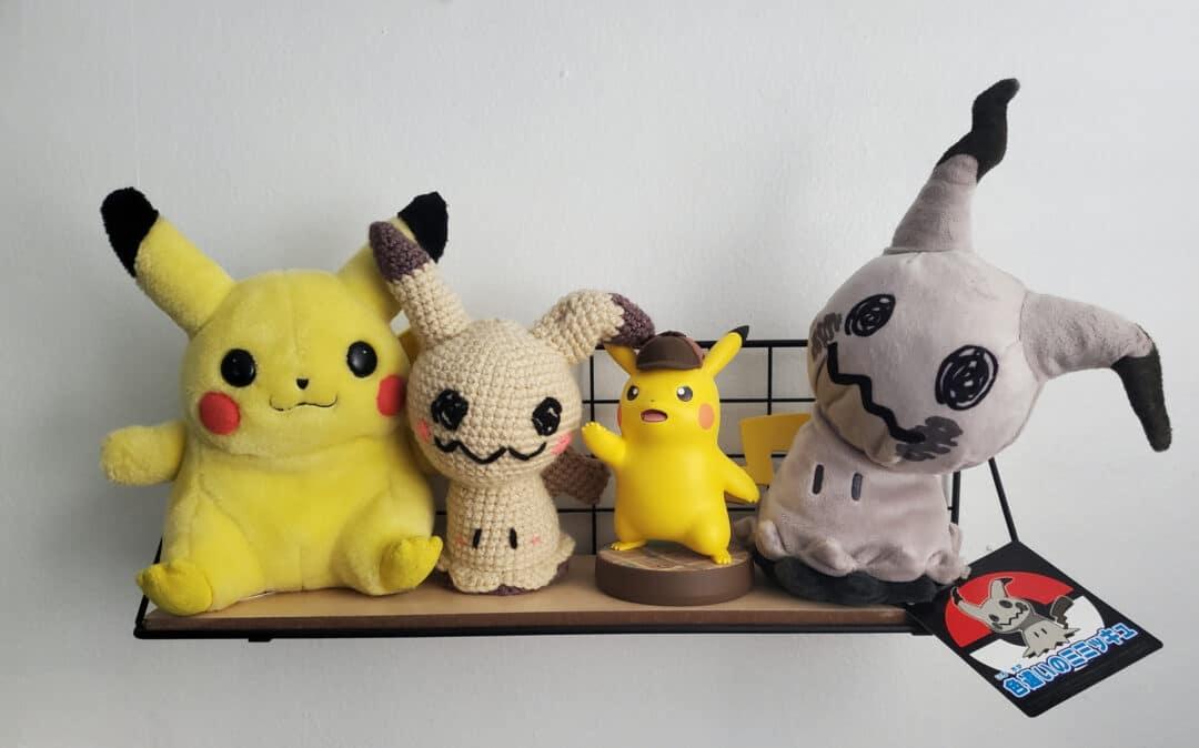 Pokémon plushes and toys sit on a shelf